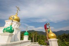 Il sacerdote ortodosso rinfresca gli incroci sulle cupole della chiesa Immagini Stock Libere da Diritti