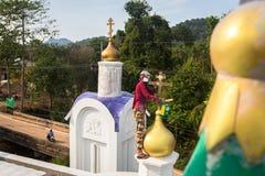 Il sacerdote ortodosso rinfresca gli incroci sulle cupole della chiesa Immagine Stock