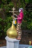 Il sacerdote ortodosso rinfresca gli incroci sulle cupole della chiesa Fotografia Stock