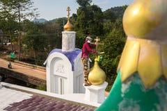 Il sacerdote ortodosso rinfresca gli incroci sulle cupole della chiesa Immagine Stock Libera da Diritti