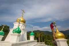 Il sacerdote ortodosso rinfresca gli incroci sulle cupole della chiesa Fotografie Stock Libere da Diritti