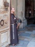 Il sacerdote sta appoggiantesi la porta all'entrata alla chiesa del sepolcro santo nella vecchia città di Gerusalemme, Israele Fotografie Stock