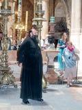 Il sacerdote sta nel corridoio nella chiesa del sepolcro santo ed accoglie gli ospiti nella vecchia città di Gerusalemme, Israele Fotografie Stock