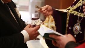 Il sacerdote trasversale consacra il bicchiere di vino stock footage