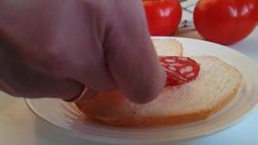 Il salame della salsiccia cade su un pomodoro di legno del fondo, le mani, pane archivi video
