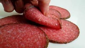 Il salame della salsiccia sulle prese bianche di una mano del fondo cade, fucilazione rallentata archivi video