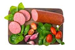 Il salame ha fumato la salsiccia con basilico, aglio ed i pomodori sul tagliere di legno isolato su fondo bianco Immagini Stock Libere da Diritti