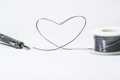 Il saldatoio ed il cavo di saldatura hanno fatto la forma del cuore fotografie stock