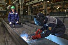 Il saldatore del lavoratore salda manualmente le lamiere di acciaio facendo uso della torcia del gas, MIG Immagine Stock
