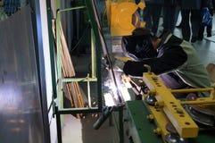 Il saldatore della saldatura ad arco realizza la saldatura del metallo nell'officina Fotografia Stock