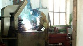 Il saldatore funzionante alla fabbrica in un vestito protettivo salda la parte, il saldatore fa la parte, la produzione, luce video d archivio