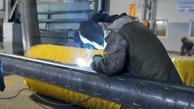 Il saldatore in maschera protettiva e camici salda le costruzioni metalliche nel negozio della fabbrica, lavorazione dei metalli  video d archivio