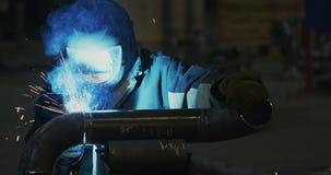 Il saldatore nella maschera di saldatura, in vestiti da lavoro alla fabbrica, salda il tubo nella stanza della fabbrica archivi video