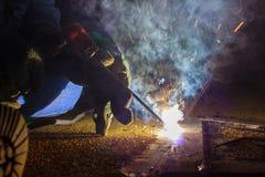 Il saldatore realizza la saldatura al di piastra metallica al pavimento del tetto di manuf fotografia stock