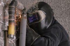 Il saldatore salda i tubi per l'installazione del gas Fotografia Stock Libera da Diritti