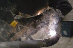 Il saldatore salda i tubi per l'installazione del gas Immagini Stock