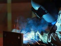 Il saldatore sta saldando la struttura d'acciaio con tutta l'attrezzatura di sicurezza in fabbrica fotografia stock