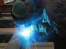 Il saldatore sta saldando la struttura d'acciaio con tutta l'attrezzatura di sicurezza in fabbrica Immagine Stock Libera da Diritti