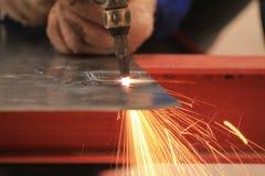 Il saldatore sta tagliando il taglio di gas del wirh del piatto d'acciaio Fotografie Stock