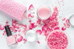 Il sale e la crema di Rosa per l'unghia si preoccupano in stazione termale sulla vista superiore del fondo bianco fotografie stock libere da diritti