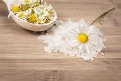 Il sale marino del giacimento detritico, camomilla fiorisce su un cucchiaio di legno Fotografia Stock
