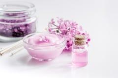 Il sale organico, la crema, l'estratto in cosmetico lilla ha messo con i fiori sul fondo bianco della tavola Immagine Stock Libera da Diritti