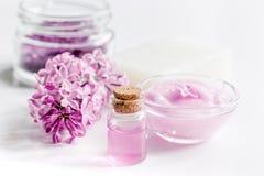 Il sale organico, la crema, l'estratto in cosmetico lilla ha messo con i fiori sul fondo bianco della tavola Fotografia Stock
