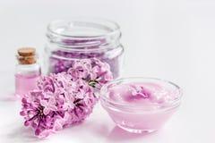 Il sale organico, la crema, l'estratto in cosmetico lilla ha messo con i fiori sul fondo bianco della tavola Fotografie Stock