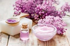 il sale organico, la crema, l'estratto in cosmetico lilla ha messo con i fiori sul fondo di legno della tavola Fotografie Stock Libere da Diritti