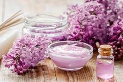 il sale organico, la crema, l'estratto in cosmetico lilla ha messo con i fiori sul fondo di legno della tavola Fotografia Stock Libera da Diritti