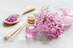 il sale organico, la crema, l'estratto in cosmetico lilla ha messo con i fiori sul fondo di pietra della tavola Fotografie Stock
