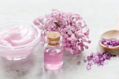 il sale organico, la crema, l'estratto in cosmetico lilla ha messo con i fiori sul fondo di pietra della tavola Immagine Stock