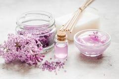 il sale organico, la crema, l'estratto in cosmetico lilla ha messo con i fiori sul fondo di pietra della tavola Immagini Stock