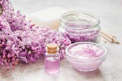 il sale organico, la crema, l'estratto in cosmetico lilla ha messo con i fiori sul fondo di pietra della tavola Fotografia Stock