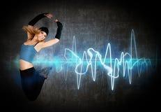 Il salto/dancing della donna al ritmo di musica Immagini Stock