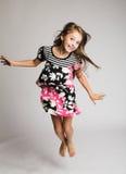 Il salto della bambina della gioia Immagine Stock