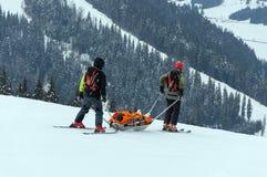 Il salvataggio del gruppo della pattuglia dello sci ha danneggiato lo sciatore con le slitte speciali nella regione delle montagn Immagini Stock Libere da Diritti