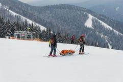 Il salvataggio del gruppo della pattuglia dello sci ha danneggiato lo sciatore con le slitte speciali nella regione delle montagn Immagini Stock