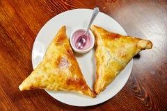 Il samosa nazionale del piatto dell'Uzbeco, due pezzi si trova su un piatto bianco Fotografie Stock Libere da Diritti