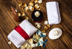 Il sapone e la pelle differente screma con gli asciugamani ed i fiori su fondo di legno immagine stock