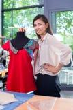 Il sarto asiatico regola la progettazione dell'indumento sul manichino fotografie stock libere da diritti