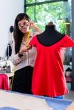 Il sarto asiatico regola la progettazione dell'indumento sul manichino fotografia stock