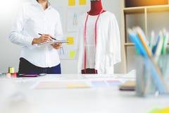 Il sarto asiatico regola la progettazione dell'indumento sul manichino nel mak dell'officina immagine stock libera da diritti