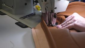 il sarto cuce il cuoio marrone in un'officina di cucito ago della macchina per cucire nel moto due aghi della macchina per cucire stock footage