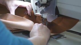 il sarto cuce il cuoio marrone in un'officina di cucito processo di cucito del cuoio sintetico ago della macchina per cucire nel  archivi video