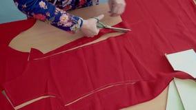 Il sarto da donna ha tagliato il tessuto rosso per i vestiti stock footage