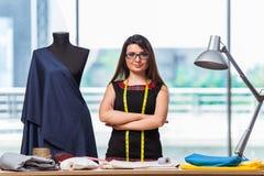 Il sarto della donna che lavora al nuovo abbigliamento Fotografie Stock