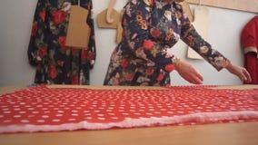 Il sarto della donna che misura con attenzione presenta i manichini sul tessuto rosso con i pois bianchi che si trovano sulla tav video d archivio