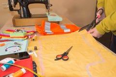 Il sarto della donna delle mani che lavora tagliando un rotolo di tessuto su cui ha segnato il modello dell'indumento lei sta fac fotografia stock libera da diritti