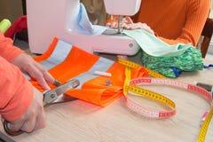 Il sarto della donna delle mani che lavora tagliando un tessuto su cui ha segnato il modello dell'indumento lei sta rendendo con  fotografie stock libere da diritti